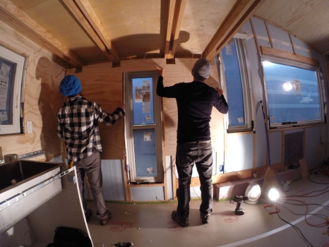 Installing a piece of paneling in the kitchen that has been notched to allow the beams to pass through.
