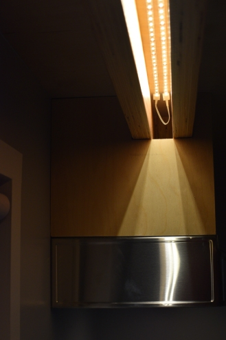 "Turns out our double loft beam detail is a nifty place to hide tape lighting. This hidden illumination sheds light onto our kitchen sink and the two flanking 12"" counter spaces."