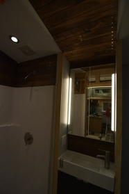 The walnut continues the bathroom sink alcove material pallet onto the ceiling.